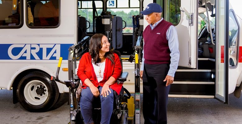 a CARTA employee helping a disabled person